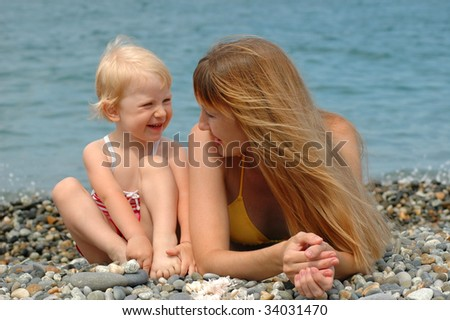 Happy woman and little girl on the beach