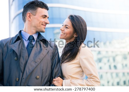 Happy woman and man flirting outdoors with glass building on background - stock photo