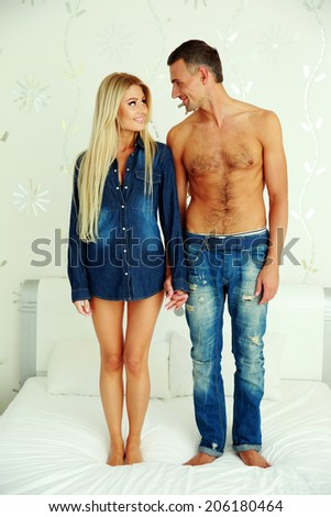 Happy woman and man standing on the bed at home - stock photo