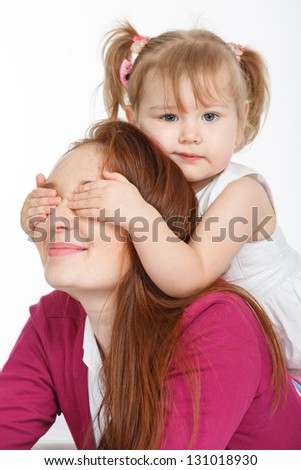 Happy woman and young girl (child) in bed smiling. Mother day concept