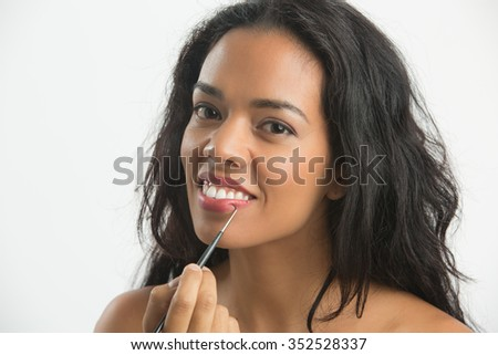 Happy woman applying makeup lips with a brush