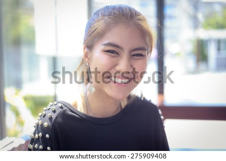 happy woman Asia Smiling white Teeth clean light background teenager gold-brown hair ,make up eye-liner and other ,wearing black T-shirt ,expression so friendly  - stock photo