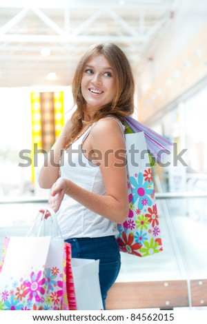 Happy woman at a shopping center with bags. Seasonal preparty shopping boom - stock photo