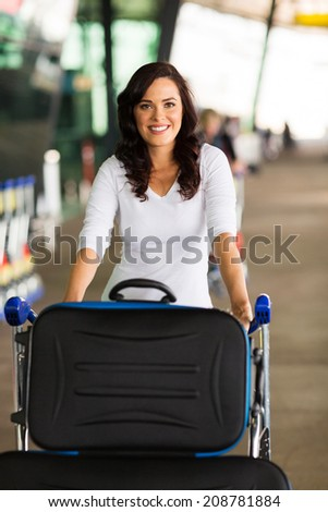 happy woman at airport with a trolley full of luggage - stock photo