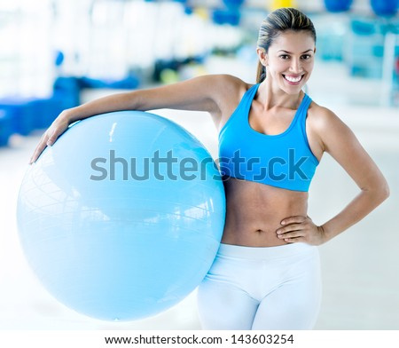 Happy woman at the gym holding a Pilates ball - stock photo