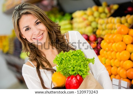 Happy woman at the supermarket buying groceries