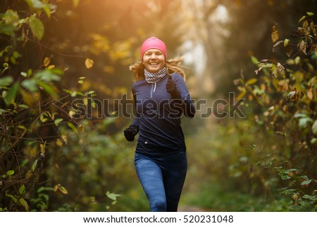 Happy woman athlete Jogging in autumn forest. Healthy lifestyle concept