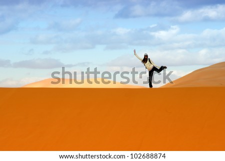 Happy woman balancing on the dunes in the Sahara desert - stock photo