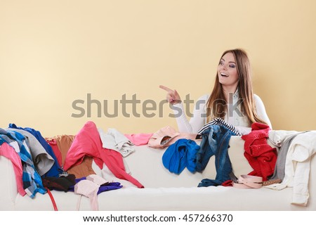 Happy woman behind sofa couch in messy living room pointing at empty blank copy space. Young girl surrounded by many stack of clothes. Disorder and mess at home. - stock photo