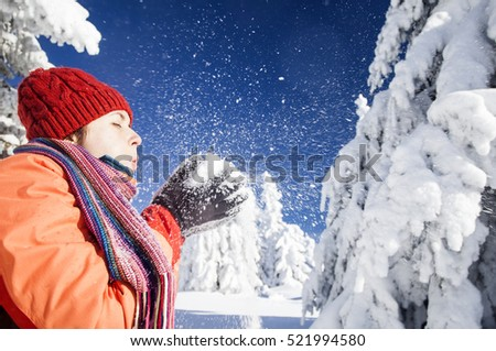 Happy woman blowing snow in winter forest. Girl having fun outdoor.