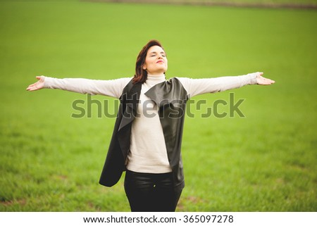 Happy woman breaths deeply with open arms in the middle of nature. - stock photo