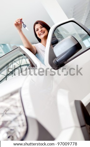 Happy woman buying a car and holding the keys - stock photo