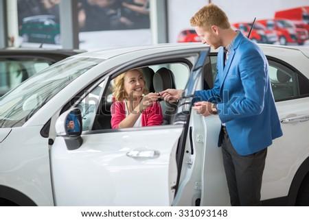 Happy woman buying a new car and salesman handling keys - stock photo