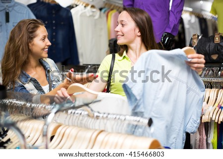 Happy woman buying shirt in shopping center for her husband