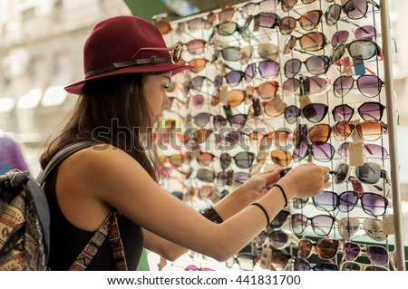 Happy woman buying sunglasses in shop on the street - stock photo