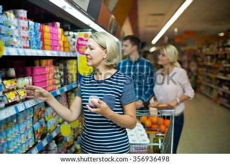 Happy woman buying sweet yoghurts in dairy section of supermarket