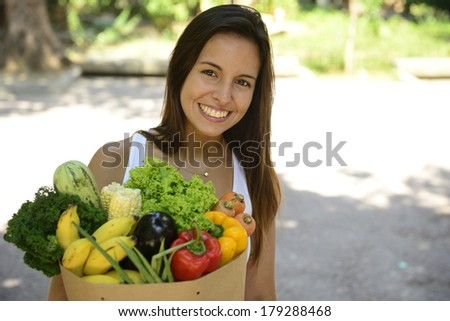 Happy woman carrying a bag full of organic food. - stock photo
