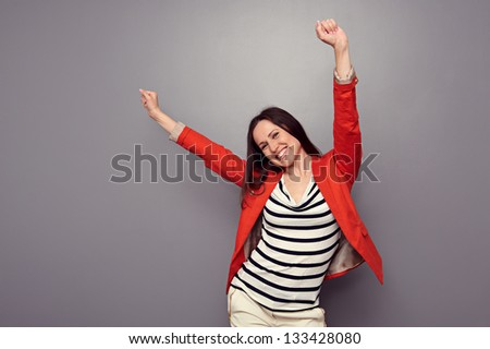 happy woman celebrating and dancing of joy winning. studio shot over dark background - stock photo