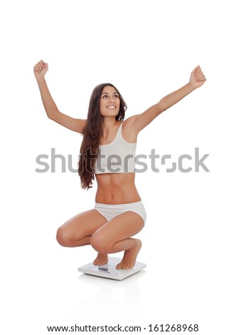 Happy woman celebrating her new weight on a scale isolated on a white background