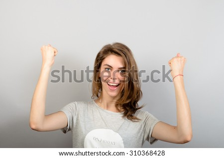 Happy woman celebrating her victory over gray background - stock photo