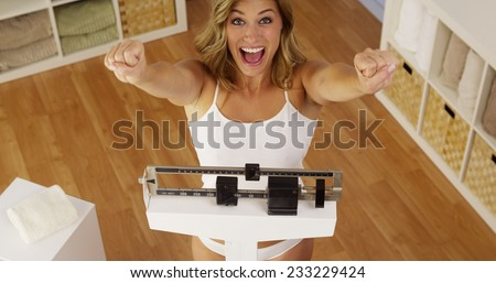 Happy woman celebrating weight loss - stock photo