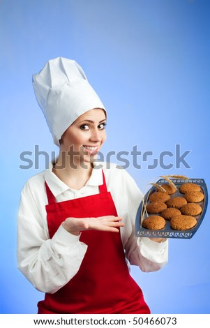 Happy woman chef offer cookies straight from oven - stock photo