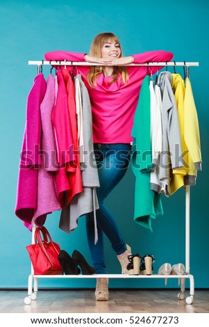 Happy woman choosing clothes in wardrobe. Girl customer shopping in mall shop. Fashion clothing sale.