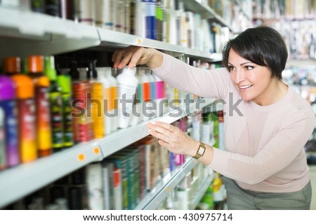 Happy woman choosing hair care products in shop and smiling