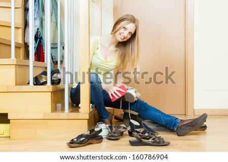 Happy woman cleaning footwear at home