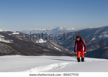 Happy woman climbing mountains in winter with beautiful lanscape behind