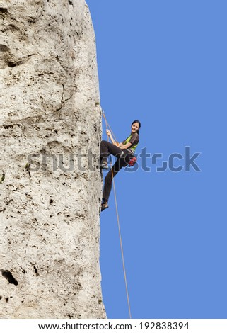 Happy woman climbing rock, active holidays.