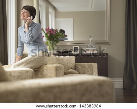 Happy woman communicating on cell phone in house
