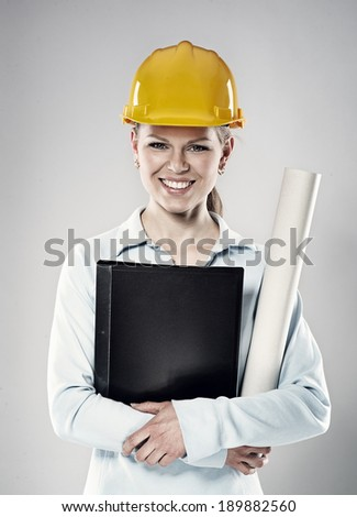 Happy woman constructor wearing yellow helmet standing with design project blueprints. Young cheerful female architect posing in studio.   - stock photo