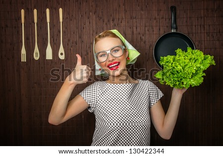 Happy woman cook with thumbs up holding salad - stock photo