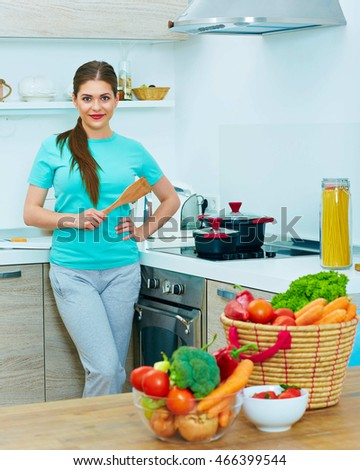Happy woman cooking food at home. Vegetables diet.