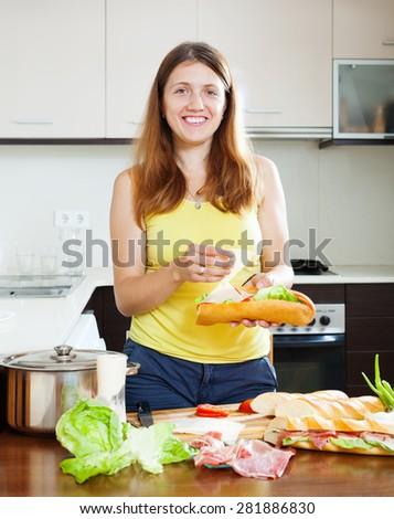 Happy woman cooking sandwiches with cheese and  hamon