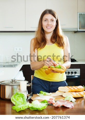 Happy woman cooking sandwiches with vegetables and  hamon in  kitchen