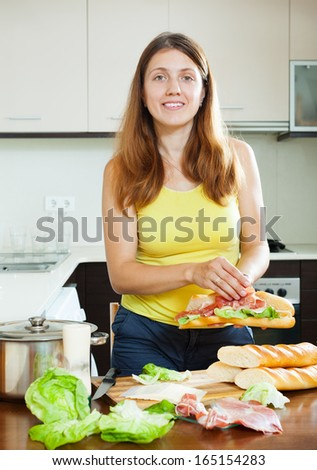 Happy woman cooking spanish sandwiches (bocadillo) with hamon in home kitchen