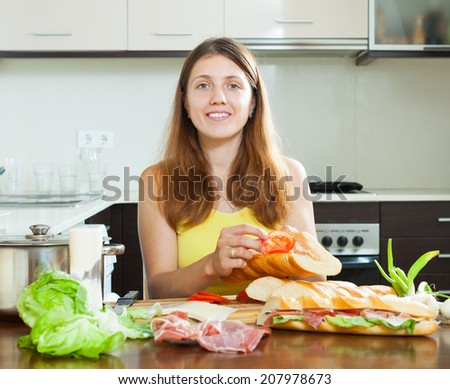 Happy woman cooking spanish sandwiches (bocadillo) with tomato and  hamon in home kitchen