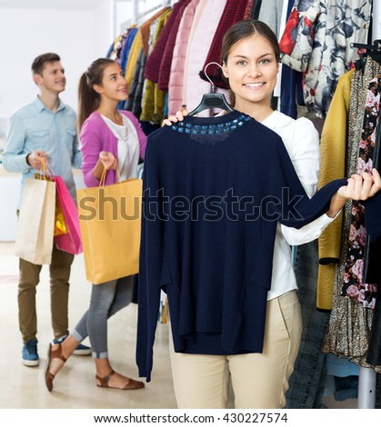 Happy woman customers chooses liked things in the boutique
