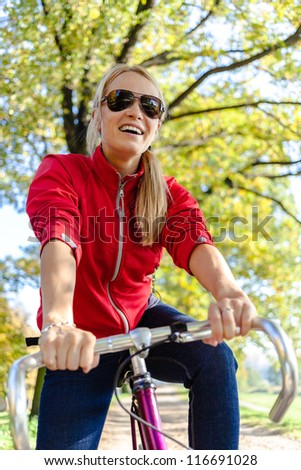 Happy woman cycling on bicycle, autumn park exercising. Young female cyclist commuting to work or relaxing in autumn nature. - stock photo