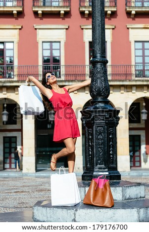 Happy woman dancing on shopping travel to Spain. Joyful girl in red dress having fun on european city. - stock photo