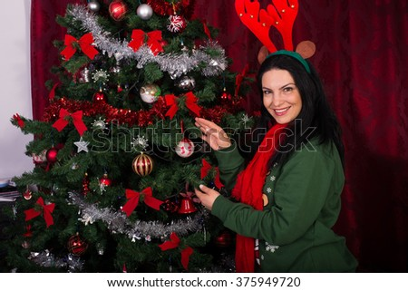 Happy woman decorate Christmas tree in her house - stock photo