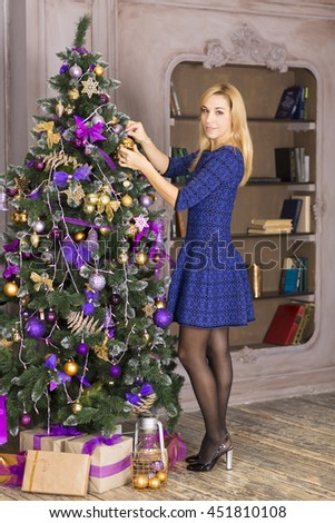 Happy woman Decorating Christmas Tree in their Home. Smiling  Woman  Celebrating Christmas or New Year. Christmas Tree Decoration.Family