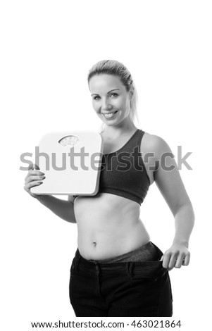 happy woman delighted with her dieting results  in big jeans showing successful weight loss holding scales, isolated on white