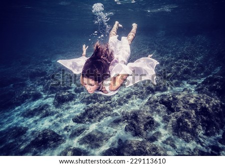 Happy woman diving to the sea bottom, swimming in stylish white dress, summertime fashion, freedom and enjoyment concept - stock photo