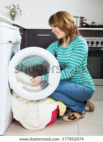 happy  woman doing laundry with washing machine at home kitchen - stock photo
