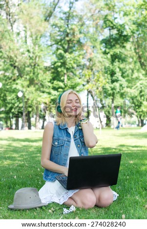 Happy woman downloading music outdoors with laptop and headphones - stock photo
