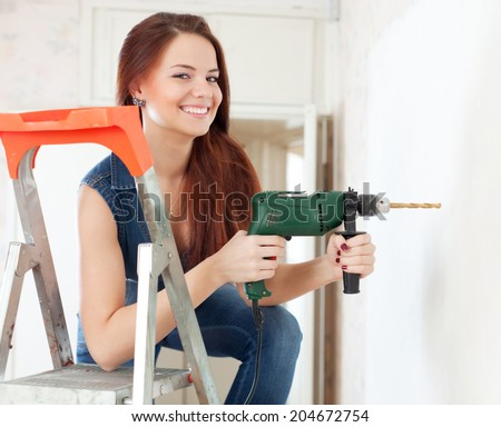 Happy woman drills hole in the wall with drill  at home - stock photo