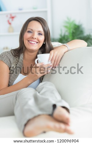 Happy woman drinking a mug on the sofa in the living room - stock photo